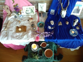 White / pink support shrine and dark blue grief shrine with objects; water and candle